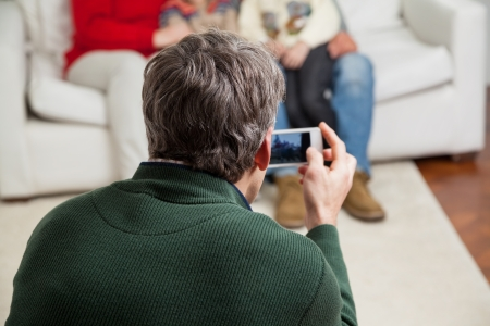 Rear view of father photographing family through smartphone at home photo