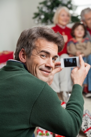 Portrait of smiling father photographing family through smartphone at home photo