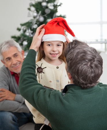 Rear view of father adjusting girls Santa hat with grandfather looking at them in house photo