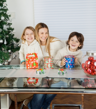 Portrait of happy children and mother with Christmas presents at home photo