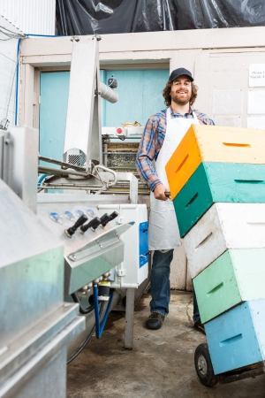 beekeeping: Portrait of happy male beekeeper holding trolley of stacked honeycomb crates in beekeeping factory