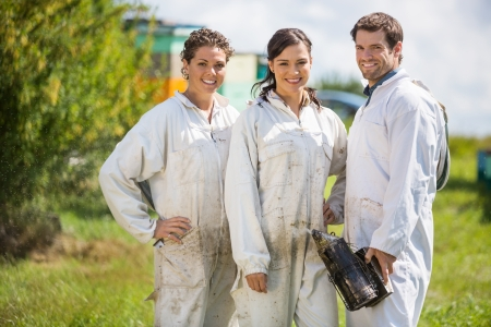 beekeeper: Team of happy male and female beekeepers standing at apiary