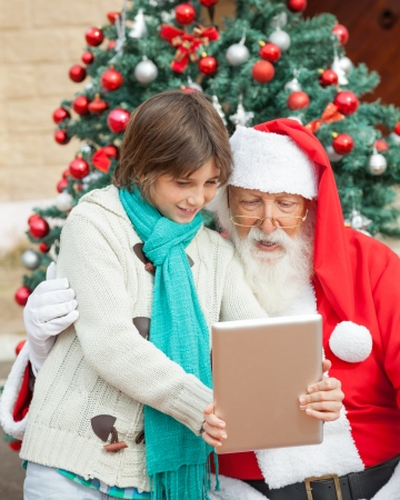 Boy showing digital tablet to Santa Claus in front of Christmas tree outdoors photo