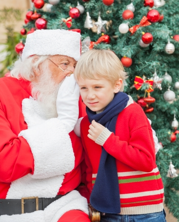 Santa Claus whispering in boys ear in front of Christmas tree photo