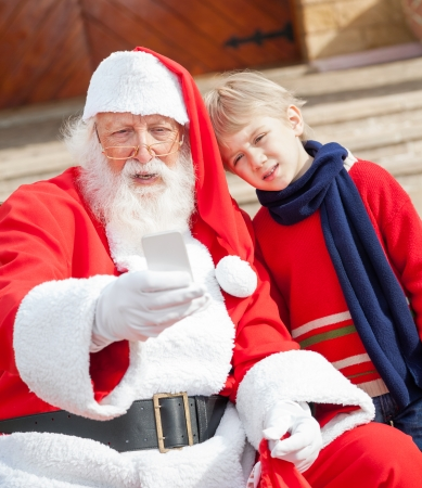 Santa Claus and boy taking selfportrait through smartphone outside house photo