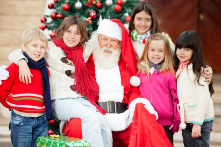 st claus: Portrait of happy Santa Claus and children outside house Stock Photo