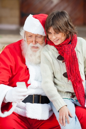 Happy Santa Claus and boy using smartphone together outdoors photo