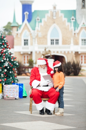 Full length of Santa Claus showing digital tablet to girl in courtyard photo