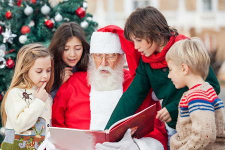 Santa Claus and children reading book against Christmas tree photo