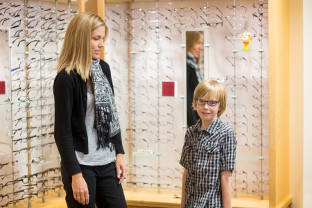 Portrait of little boy wearing spectacles while mother looking at him in shop photo