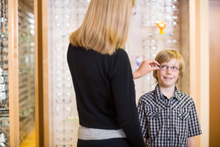 Rear view of mother trying spectacles on preadolescent son at shop photo
