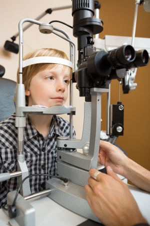 Preadolescent boy having his eyes examined with slit lamp by doctor photo