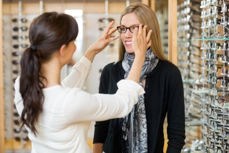 Young salesgirl assisting female customer to in wearing glasses at shop