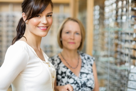 salesgirl: Portrait of beautiful salesgirl with senior woman in optician store