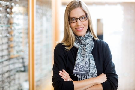 Portrait of beautiful woman wearing glasses with arms crossed in optician store photo