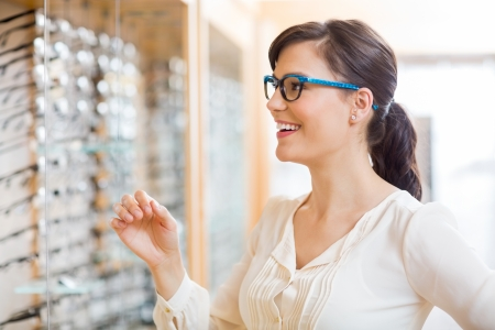 optician: Happy young woman trying new glasses at optician store Stock Photo