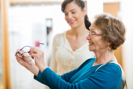 salesgirl: Senior woman holding new glasses with salesgirl in background at store