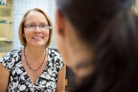 Optician measuring mature woman's eyeglasses in store Stock Photo - 23726553