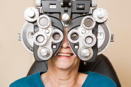 eye exam: Happy senior woman looking through phoropter during eye exam