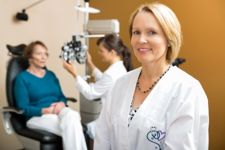 eye doctor: Portrait of confident eye doctor with colleague examining patient in background Stock Photo