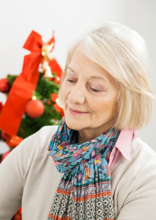 Senior woman in front of Christmas tree at home photo