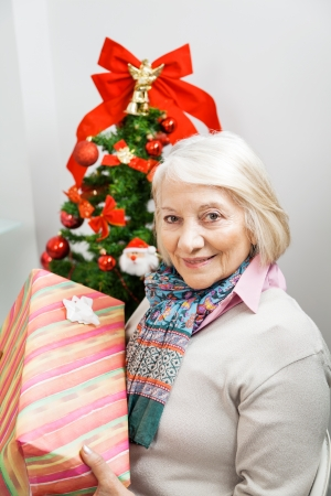 Portrait of smiling senior woman holding present by Christmas tree at home photo