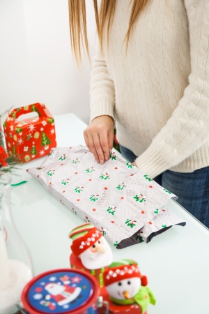 Midsection of mid adult woman packing Christmas gifts at home photo