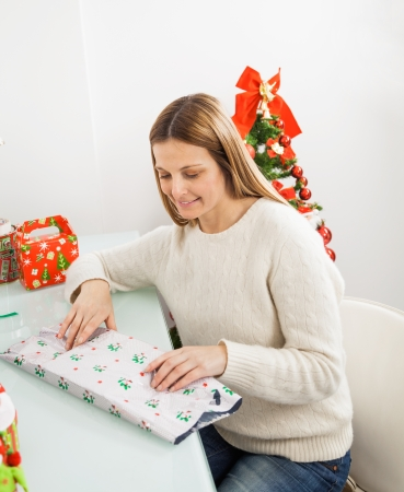 Mid adult woman wrapping Christmas presents at home photo