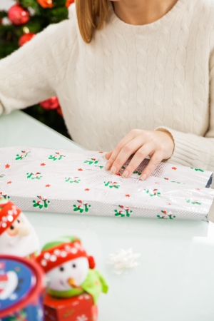 Midsection of mid adult woman packing Christmas present at home photo