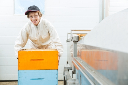 beekeeping: Portrait of senior female beekeeper with honeycomb crates at beekeeping factory