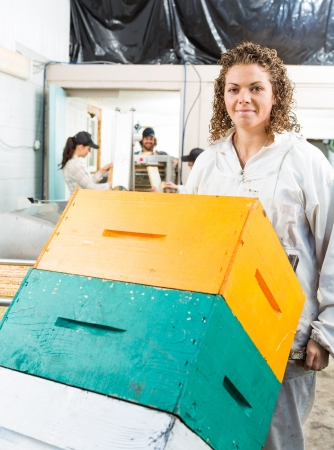 Portrait of female beekeeper holding trolley of stacked honeycomb crates in beekeeping factory photo