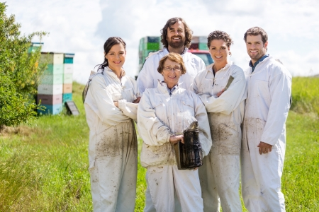 apiary: Team of confident male and female beekeepers standing together at apiary