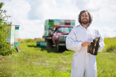 beekeeper: Portrait of happy beekeeper in protective clothing holding smoker while standing at apiary Stock Photo