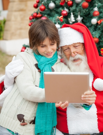 Santa Claus using digital tablet with boy in front of Christmas tree photo