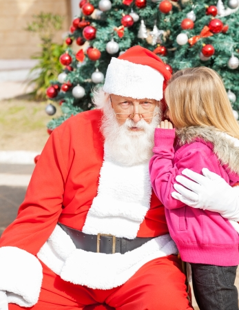 Girl telling wish in Santa Clauss ear in front of Christmas tree photo