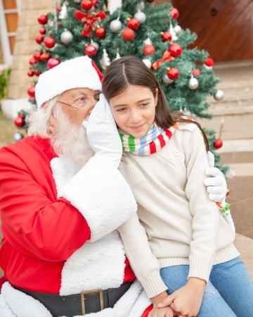 Santa Claus whispering in girls ear against Christmas tree photo