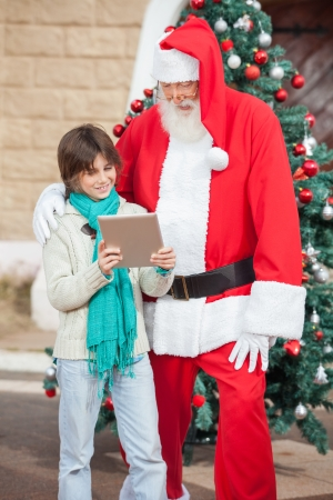 Boy showing digital tablet to Santa Claus in front of Christmas tree photo