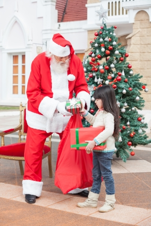 Full length of girl taking presents from Santa Claus against house photo
