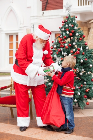 Full length of Santa Claus giving present to boy in courtyard photo