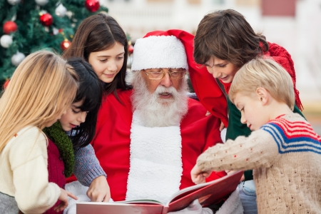 Ni�os y Santa Claus libro de lectura en el patio photo