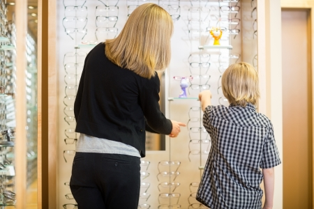 Rear view of mother and son choosing spectacles in shop photo