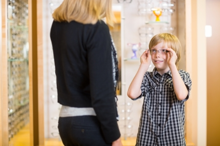 Preadolescent boy looking at mother while trying on spectacles in shop photo