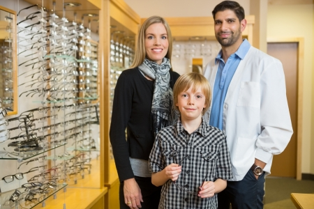Portrait of boy with optometrist and mother standing in store photo
