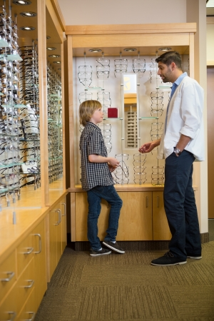 Profile of mid adult male optometrist and boy communicating in store photo