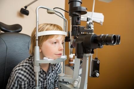 slit: Boy preadolescentes sometido a estudio del ojo con l�mpara de hendidura en la tienda Foto de archivo