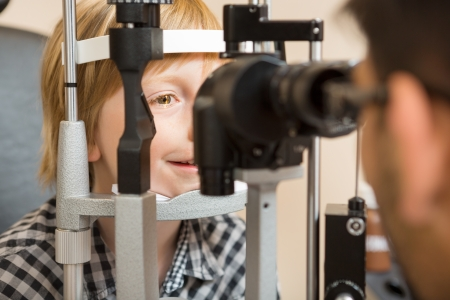 slit: Preadolescent boys eyes being examined by slit lamp in store