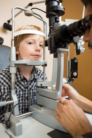 preadolescent: Portrait of preadolescent boy having his eyes tested with slit lamp by doctor
