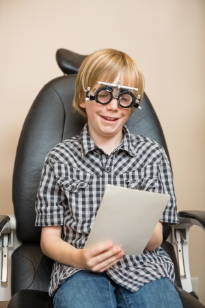 Smiling preadolescent boy with trial frame reading test chart while sitting on chair at optician photo