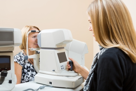 Young Optometrist measuring patients eye pressure with tonometer photo