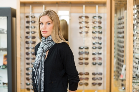 Portrait of mid adult woman standing in glasses store photo